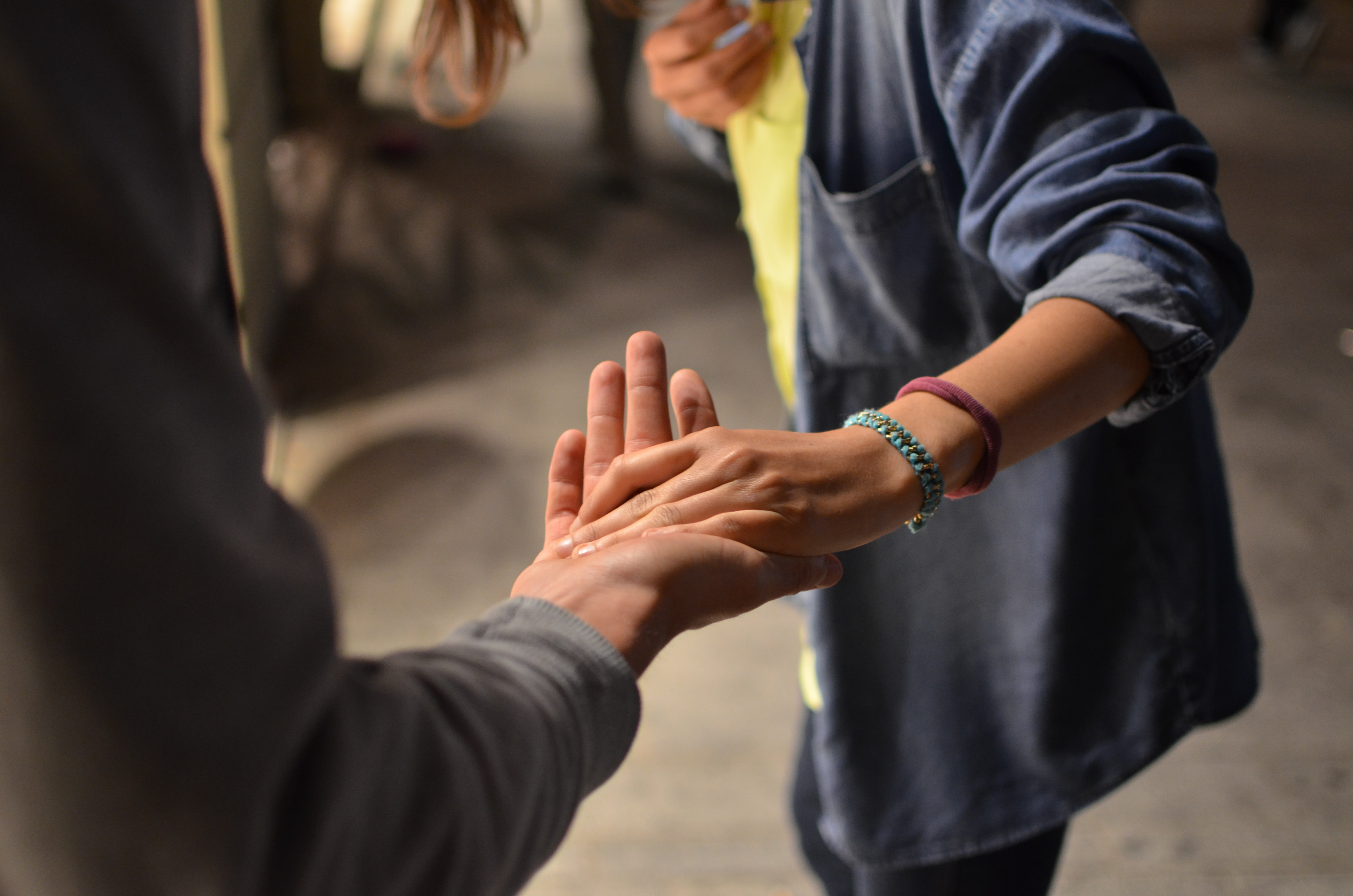Cover image used in the article that this post links to. The photo shows the torsos of two people, with the focus on their hands. One person is reaching out, palm up, from the foreground, the other is resting their hand on top of the offered hand.