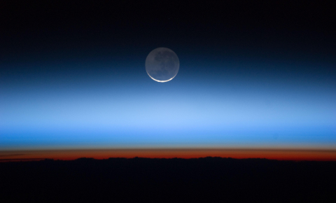 Astronauts on the International Space Station are treated to stunning views, including a crescent moon hanging above the gaseous layers of Earth's atmosphere. Image credit - NASA's Earth Observatory, licensed under CC BY 2.0