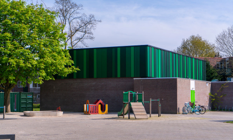 A coat of special green paint used on panels at a school gym in Almere, the Netherlands, helps the panels absorb sunlight for heating and for hot water. Image credit - Emergo