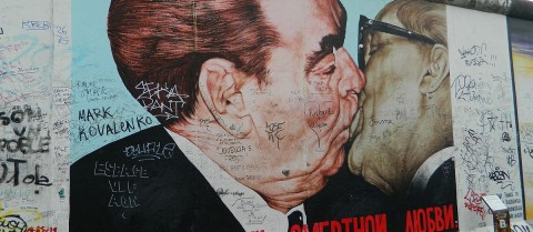 The 'Fraternal Kiss' mural, by Soviet artist Dmitri Vrubel, emblematic of the Cold War, appeared on the Berlin East Side Gallery, Berlin Wall, 1990. Image credit - Freepenguin, licensed under CC BY-SA 3.0
